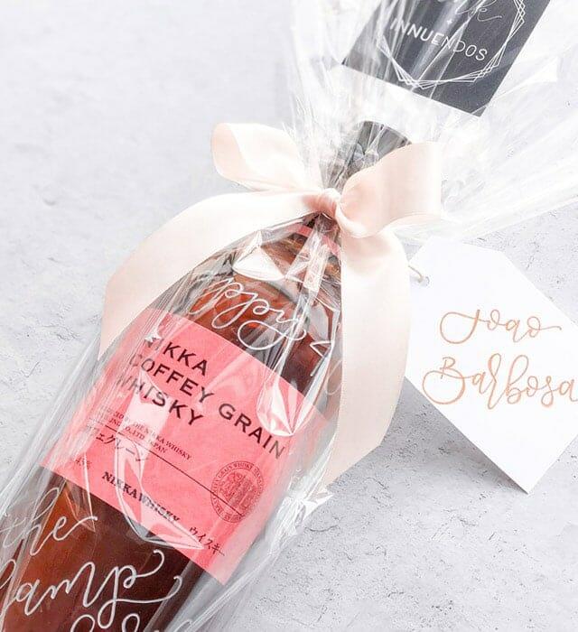 botella de whisky grabada de Ink & Innuendos envuelta en papel celofán y terminada con cinta de raso y etiqueta