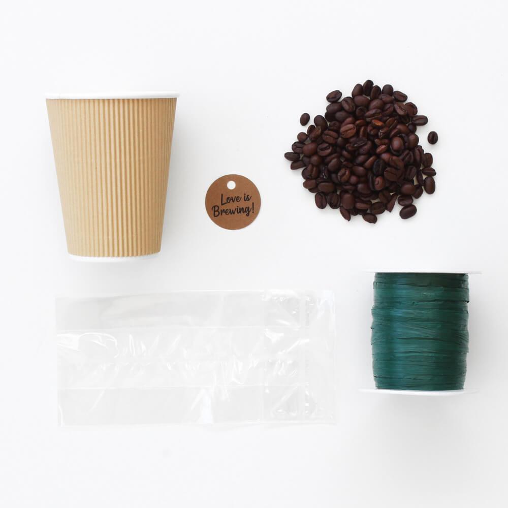 diseño plano de regalo de taza de café con bolsa de violonchelo, cinta de rafia, posos de café y etiqueta.
