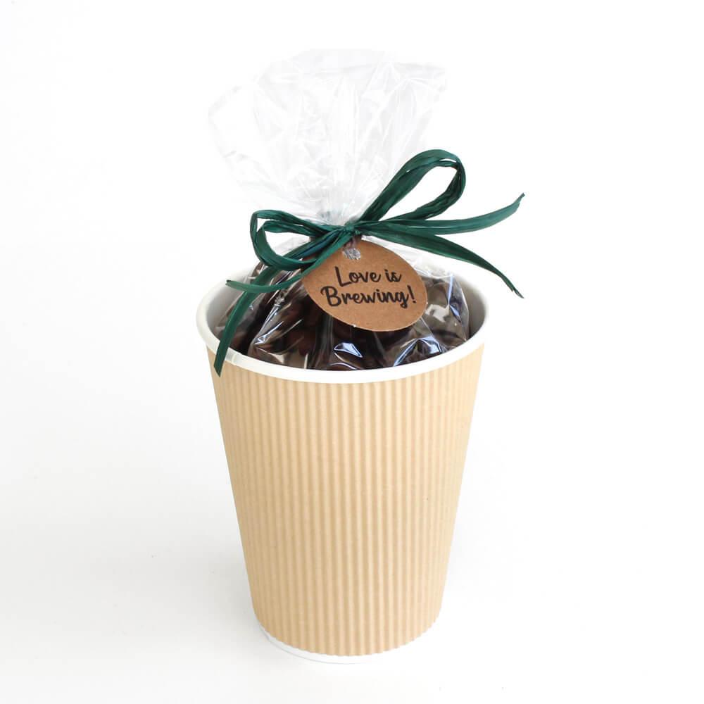 regalo de café en una taza con cinta de rafia y etiqueta.