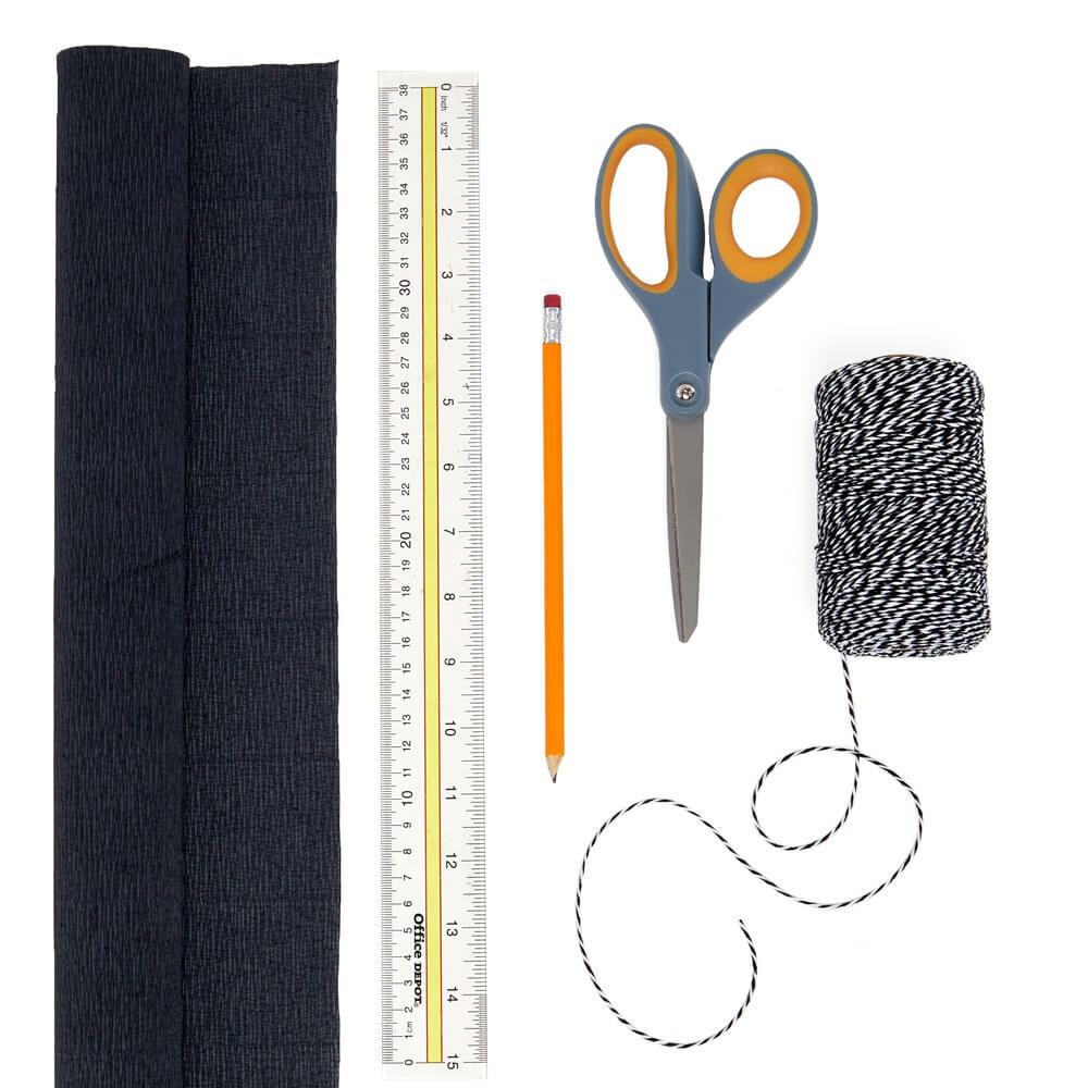 Manualidades de suministros planos de un rollo de crepé del mercado de papel, rollo de hilo blanco y negro, una regla, lápiz y tijeras
